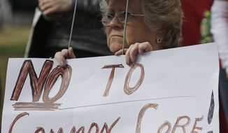 **FILE** Alabama Tea Party member Kay Day of Irvington, Ala., demonstrates in front of the Alabama Statehouse in Montgomery, Ala., as lawmakers gathered inside on Feb. 5, 2013, the first day of their regular legislative session. Day was protesting Alabama's efforts in the Common Core education guidelines. (Associated Press)