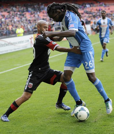 D.C. United midfielder Kyle Porter, left, battles for the ball against Philadelphia Union midfielder Keon Daniel (26) during the second half of an MLS soccer game on Sunday, April 21, 2013, in Washington. The Union won 3-2. (AP Photo/Nick Wass)