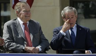 Former president George W. Bush wipes a tear after his speech during the dedication of the George W. Bush Presidential Center in Dallas on April 25, 2013. His father, former president George H.W. Bush, is at left. (Associated Press)