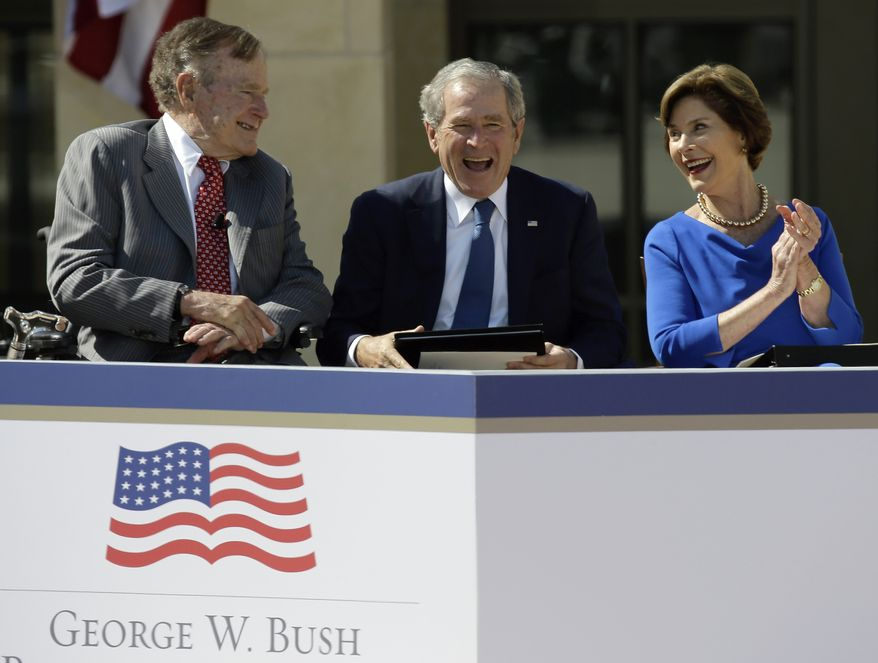 Former President George W. Bush, center, shares a laugh with his wife, former first lady Laura Bush, and father, former President George H.W. Bush, during the dedication of the George W. Bush Presidential Center, Thursday, April 25, 2013, in Dallas. (AP Photo/David J. Phillip)