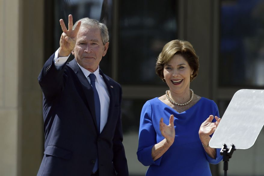 """Former President George W. Bush, accompanied by his wife former first lady Laura Bush, flashes the """"W"""" sign after his speech during the dedication of the George W. Bush Presidential Center, Thursday, April 25, 2013, in Dallas. (AP Photo/David J. Phillip)"""