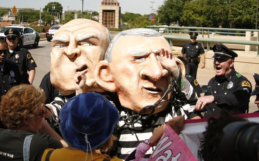 Two protesters wearing costumes near the opening of the George W. Bush Presidential Center are asked by Dallas Police to remain on the sidewalk as The George W. Bush Presidential Center is dedicated in Dallas on Thursday, April 25, 2013. The two protesters wearing costumes were arrested.  (AP Photo/Mike Fuentes)