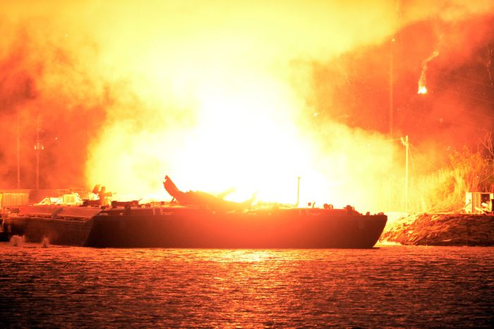 A massive explosion at 3 a.m. EDT on one of the two barges still ablaze in the Mobile River in Mobile, Ala., on Thursday, April 25, 2013. Three people were injured in the blast. (AP Photo John David Mercer)