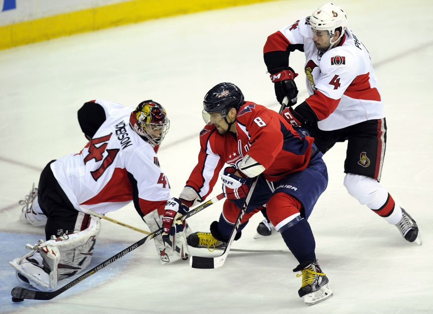 Washington Capitals left wing Alex Ovechkin (8), of Russia, skates past Ottawa Senators goalie Craig Anderson (41) and Chris Phillips (4) en route to scoring a goal during the third period of an NHL hockey game, Thursday, April 25, 2013, in Washington. Ottawa won 2-1 in overtime. (AP Photo/Nick Wass)
