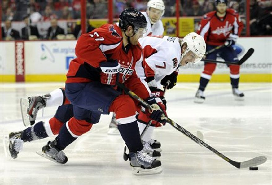 Ottawa Senators center Kyle Turris (7) chases the puck against Washington Capitals defenseman Karl Alzner, left, during the second period of an NHL hockey game, Thursday, April 25, 2013, in Washington. (AP Photo/Nick Wass)