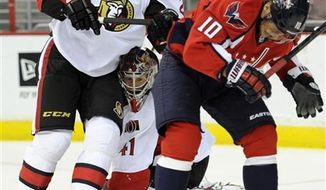 Ottawa Senators goalie Craig Anderson, center, looks for the puck between Jared Cowen, left, and Washington Capitals left wing Martin Erat (10), of the Czech Republic, during the first period of an NHL hockey game, Thursday, April 25, 2013, in Washington. (AP Photo/Nick Wass)