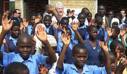 Former US President Bill Clinton smiles in a group picture with Ugandan school children of  I am Building Tomorrow Academy of Gita in Matugga, about 50km from Kampala, Uganda, Friday, July 20, 2012. (AP Photo/Ronald Kabuubi)