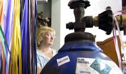 **FILE** Lee Medina, an employee at Dan D Party Corner in Cheyenne, Wyo., stands near a close-to-empty helium tank used to fill balloons on Sept. 22, 2011. (Associated Press)