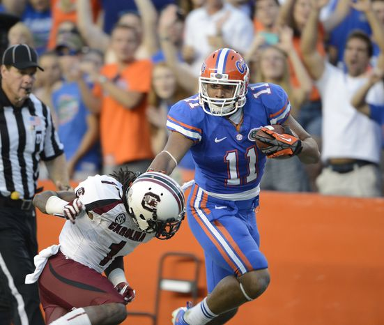 Florida's Jordan Reed (11) stiff-arms South Carolina's Ace Sanders on a punt return during the second half of an NCAA college football game Saturday, Oct. 20, 2012, in Gainesville, Fla. Florida won 44-11. (AP Photo/Phil Sandlin)