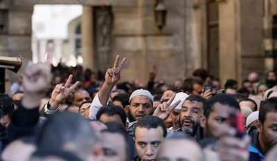 "Muslim Brotherhood and Egyptian President Morsi supporters chant slogans during a funeral of three victims who were killed during Wednesday's clashes outside Al-Azhar mosque, the highest Islamic Sunni institution, Friday, Dec. 7, 2012. During the funeral, thousands Islamist mourners chanted, ""with blood and soul, we redeem Islam,"" pumping their fists in the air. ""Egypt is Islamic, it will not be secular, it will not be liberal,"" they chanted as they walked in a funeral procession that filled streets around Al-Azhar mosque. Thousands of Egyptians took to the streets after Friday midday prayers in rival rallies and marches across Cairo, as the standoff deepened over what opponents call the Islamist president's power grab, raising the specter of more violence. (AP Photo/Hassan Ammar)"