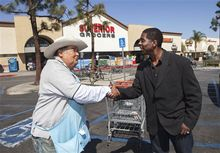 Former child actor Rodney Allen Rippy, a losing candidate for Mayor of  Compton, Ca., poses for a photo with an unidentified supporter near Compton City Hall. (AP Photo/Damian Dovarganes)
