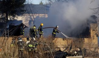 Ministry for Emergency Situations workers and firefighters work at a site of a fire of a psychiatric hospital Friday morning, April 26, 2013. At least 38 people died in the fire in the psychiatric hospital outside Moscow late Thursday night. (AP Photo/Pavel Sergeyev)