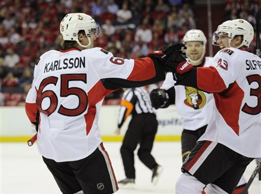 Ottawa Senators left wing Jakob Silfverberg, right, of Sweden, celebrates his goal with teammate Erik Karlsson (65), of Sweden, who got an assist on the goal, during the second period of an NHL hockey game against the Washington Capitals, Thursday, April 25, 2013, in Washington. (AP Photo/Nick Wass)
