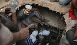 A Bangladeshi rescuer looks out from a hole cut in the concrete as he searches for survivors on Thursday, April 25, 2013, at the site of a building that collapsed the day before in Savar, near Dhaka, Bangladesh. (AP Photo/Kevin Frayer)
