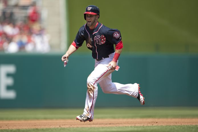 Washington Nationals' Bryce Harper runs towards home to score a run on a single hit by teammate Ian Desmond during the third inning of a baseball game against the Cincinnati Reds at Nationals Park on Saturday, April 27, 2013, in Washington. (AP Photo/Evan Vucci)
