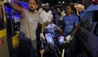 Pakistani volunteers rush an injured person to hospital following an explosion in Karachi, Pakistan on Friday, April 26, 2013. A bomb planted near the office of a political party threatened by the Taliban has killed many people in southern Pakistan, police said. (AP Photo/Shakil Adil)