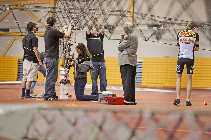 Second year grad student Elizabeth Weiner, right, watches as UMD student and volunteer pilot Colin Gore, center, performs a test flight as students with the University of Maryland attempt to win the $250,000 AHS Sikorsky Prize using their human-powered helicopter at the Prince George's County Sports and Learning Complex in Landover, Md., Sunday, April 28, 2013. The helicopter has already set records for flight time and altitude. (Andrew Harnik/The Washington Times)