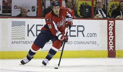 Washington Capitals defenseman Steven Oleksy (61) brings the puck up the ice during the second period of an NHL hockey game against the Carolina Hurricanes on Thursday, April 11, 2013, in Washington. (AP Photo/Evan Vucci)
