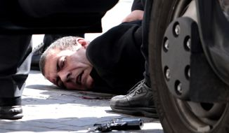 A man believed to be the assailant lies on the ground detained by police after a shootout outside the Chigi Palace, the office of Italy's premier, in Rome on Sunday, April 28, 2013. Two paramilitary police officers were shot and wounded in the incident. (AP Photo/Mauro Scrobogna, Lapresse)