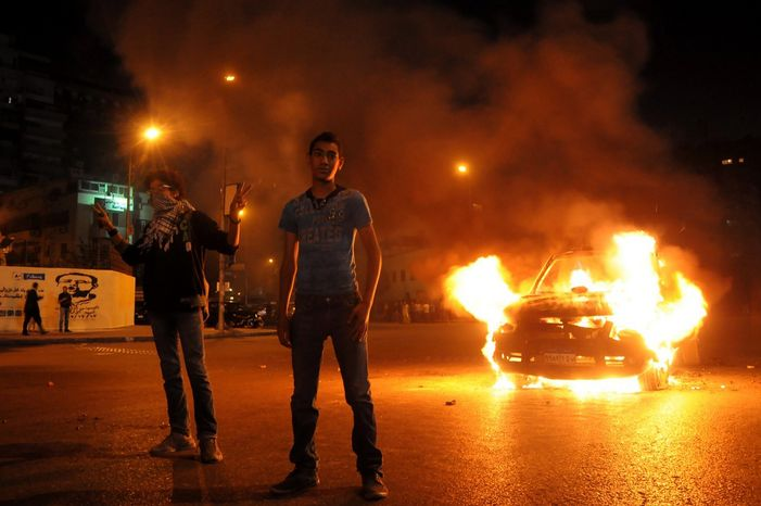 Egyptian protesters pose next to a police vehicle set afire during clashes outside the presidential palace in Cairo on Friday, April 26, 2013. Dozens of mostly masked protesters hurled stones and firebombs in clashes with riot police. Protests have become a weekly ro