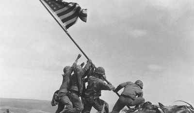 U.S. Marines of the 28th Regiment, 5th Division, raise the American flag atop Mount Suribachi on Iwo Jima on Feb. 23, 1945, in a Pulitzer Prize-winning photo by Associated Press photographer Joe Rosenthal. Alan Wood, a World War II veteran who provided the flag, has died at age 90. Mr. Wood was in charge of communications on a landing ship on Iwo Jima's shores when a Marine asked him for the biggest flag he could find. Mr. Wood handed him a flag he had found at Pearl Harbor. (AP Photo/Joe Rosenthal)