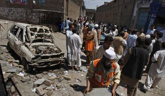 People gather at the site of an explosion outside an election office of a candidate in Peshawar, Pakistan, on Sunday, April 28, 2013. The Pakistani Taliban detonated bombs at the campaign offices of two politicians in the country's northwest, police said, killing many people in an escalation of attacks on secular, left-leaning political parties. (AP Photo/Mohammad Sajjad)