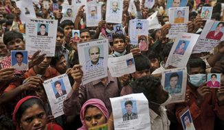 ** FILE ** Bangladeshi relatives of missing workers in a building that collapsed Wednesday hold pictures of their family members in Savar, near Dhaka, Bangladesh, Sunday, April 28, 2013. (AP Photo/Kevin Frayer)