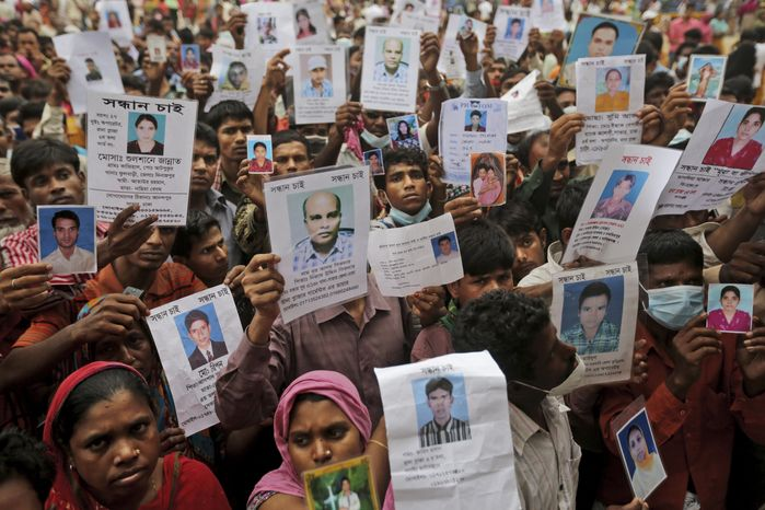 ** FILE ** Bangladeshi relatives of missing workers in a building that collapsed Wednesday hold pictures of their family members in Savar, near Dhaka, Banglades