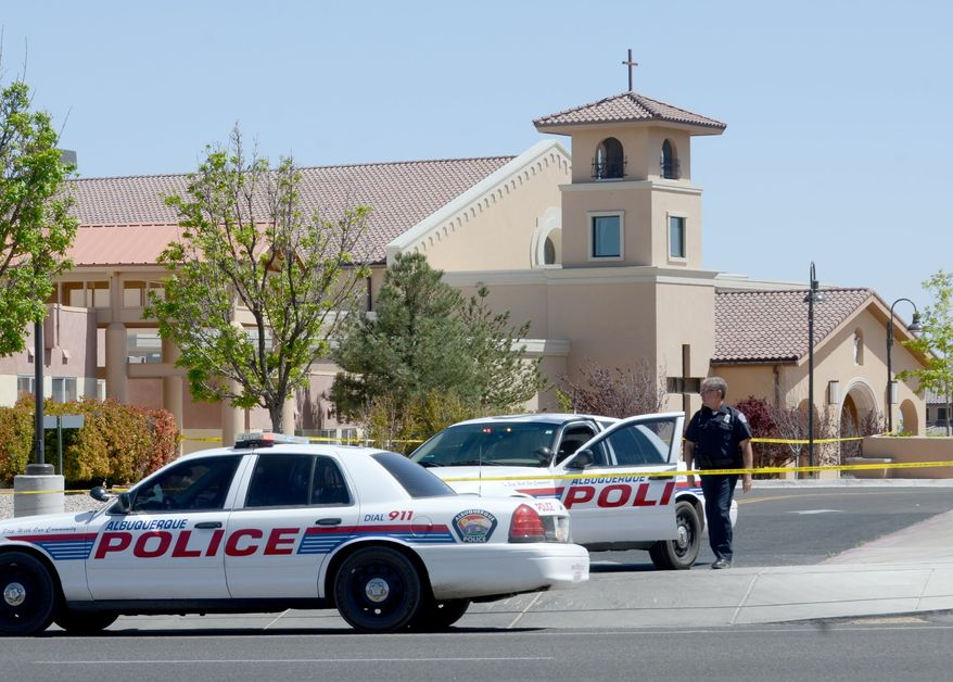 An Albuquerque Police officer walks behind the tape at St. Jude Thaddeus Catholic Church, Sunday April 28, 2013, in Albuquerque, N.M., the scene of a multiple stabbing at the conclusion of morning services. (AP Photo/Albuquerque Journal, Dean Hanson)