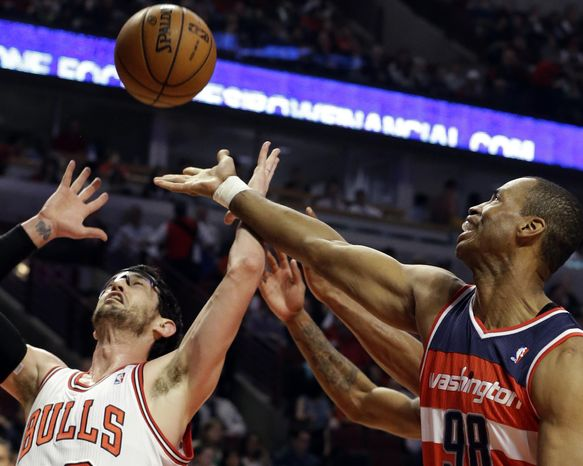 **FILE** Washington Wizards center Jason Collins (right) battles for a rebound against Chicago Bulls guard Kirk Hinrich during the first half of the Bulls' 95-92 win in Chicago on April 17, 2013. (Associated Press)