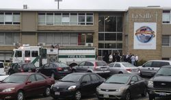 ** FILE ** Police and firefighters gather outside La Salle High School, Monday, April 29, 2013, in Cincinnati, after a high school student pulled out a gun and shot himself in a classroom. The Hamilton County sheriff's office says the youth was taken to a hospital with a self-inflicted wound. (AP Photo/Cincinnati Enquirer, Glenn Hartong)