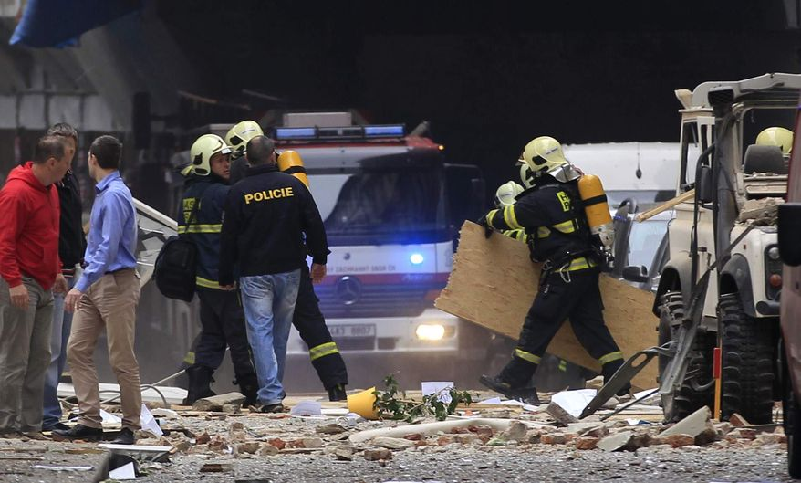 Policemen and firefighters inspect the scene of an explosion in downtown Prague, Czech Republic, Monday, April 29, 2013. Police said a powerful explosion has damaged a building in the center of the Czech capital, and they believe some people are buried in the rubble. (AP Photo/Petr David Josek)