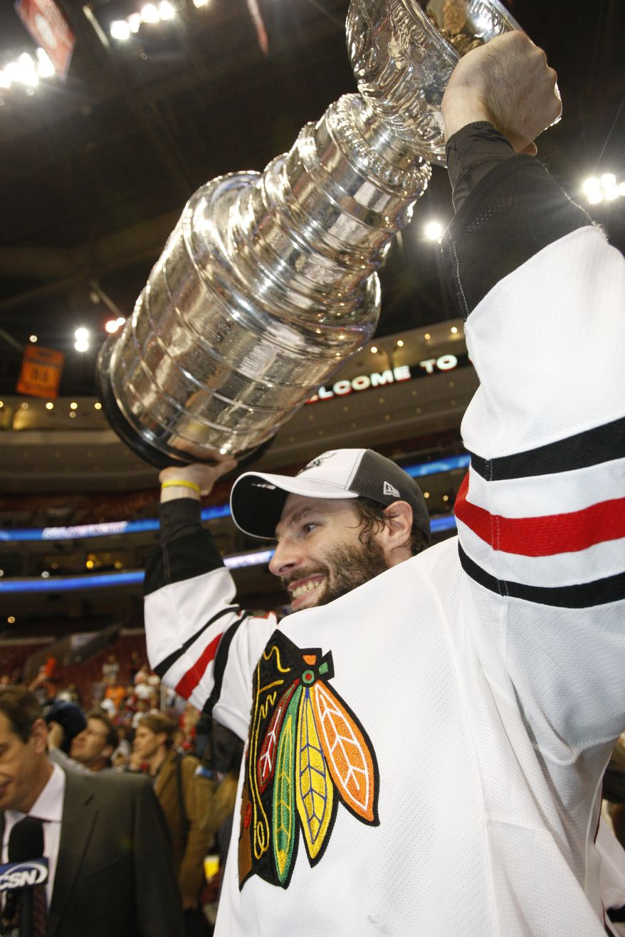Chicago Blackhawks right wing Troy Brouwer lifts the Stanley Cup after the Chicago Blackhawks beat the Philadelphia Flyers 4-3 in overtime to win Game 6 of the NHL Stanley Cup hockey finals on Wednesday, June 9, 2010, in Philadelphia. (AP Photo/Kathy Willens)