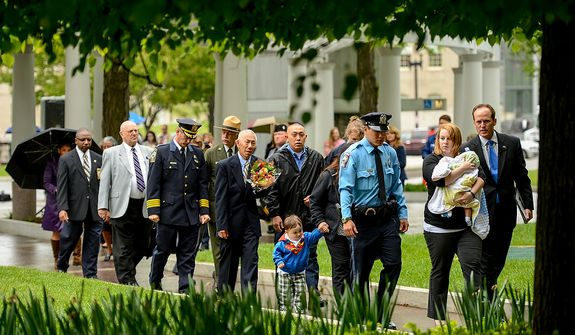 Family members of Prince William County Police Officer Chris Yung are escorted during a ceremony, to unveil the name of slain Prince William County Police Officer Chris Yung on the wall of the National Law Enforcement Memorial, Washington, D.C., Monday, April 29, 2013. Yung was killed in a motorcycle accident while responding to a separate car crash New Years Eve last year. (Andrew Harnik/The Washington Times)