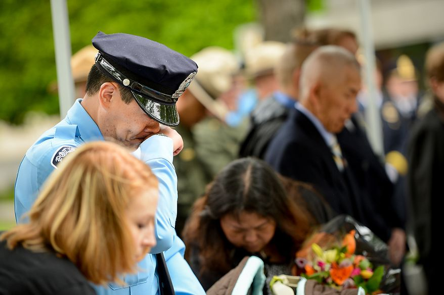 Officer Dale Yung becomes emotional during a ceremony to unveil the name of his brother, slain Prince William County Police Officer Chris Yung on the wall of the National Law Enforcement Memorial, Washington, D.C., Monday, April 29, 2013. Yung was killed in a motorcycle accident while responding to a separate car crash New Years Eve last year. (Andrew Harnik/The Washington Times)