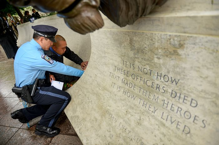 Prince William's County Police Officer Dale Yung and Brian Yung make a rubbing of their slain brother, Prince William County Police Officer Chris Yung during a ceremony to unveil his name on the wall of the National Law Enforcement Memorial, Washington, D.C., Monday, April 29, 2013. Yung was killed