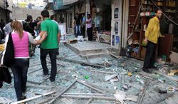Syrians walk on shattered glass from damaged shops at the scene of a powerful explosion that occurred in the central district of Marjeh in Damascus, Syria, on Tuesday, April 30, 2013. (AP Photo/SANA)