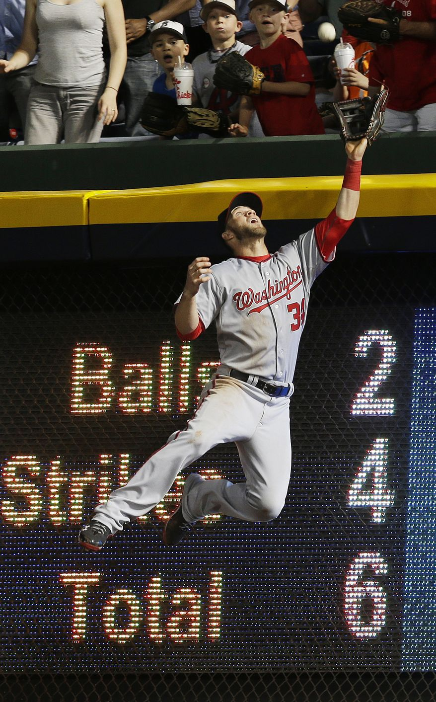 Bryce Harper leaps to make what could've been a home run-robbing catch on a ball hit by Braves pitcher Tim Hudson on Tuesday night. Harper collided with the scoreboard, though, and the ball popped out of his glove and over the wall in the Nationals' loss. (Associated Press photo)