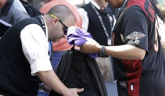 **FILE** In this photo taken Wednesday, April 24, 2013, a security guard checks the backpack of a fan entering AT&T Park before a baseball game between the San Francisco Giants and the Arizona Diamondbacks in San Francisco. Major League Baseball's previously scheduled security meeting in New York took on added importance in the aftermath of the marathon bombs. Each team sets its own security standards, although clubs might consider cutting the size of the general major league limitation on bags from 16x16x8 inches to something less.(AP Photo/Jeff Chiu)