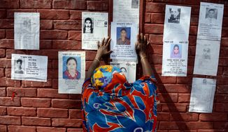 A woman grieves as she sticks a poster of a portrait of her family member on the wall of a school turned make-shift morgue on Tuesday April, 30, 2013 in Savar, near Dhaka, Bangladesh. (AP Photo/Ismail Ferdous)
