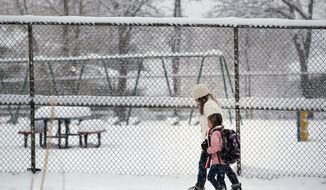 ** FILE ** An elementary school student is walked to class as a spring storm dropped snow over Boulder, Colo., Tuesday April 23, 2013. (AP Photo/Brennan Linsley)