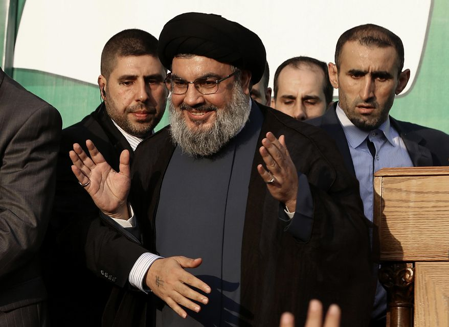 ** FILE ** In this Monday, Sept. 17, 2012, file photo, Hezbollah leader Sheik Hassan Nasrallah, center, waves to his supporters, in the southern suburb of Beirut, Lebanon. (AP Photo/Hussein Malla, File)