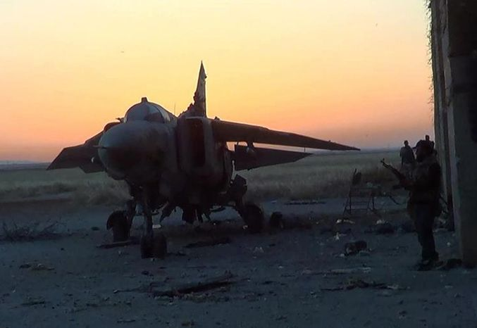 This citizen journalism image provided by the Syrian Revolution Against Bashar Assad, which has been authenticated based on its contents and other AP reporting, shows Syrian rebels, right, standing next a damaged warplane, at Abu Dhour military airbase, which is besieged by the rebels in the northern province of Idlib, Syria, Tuesday, April 30, 2013. (AP Photo/The Syrian Revolution Against Bashar Assad)
