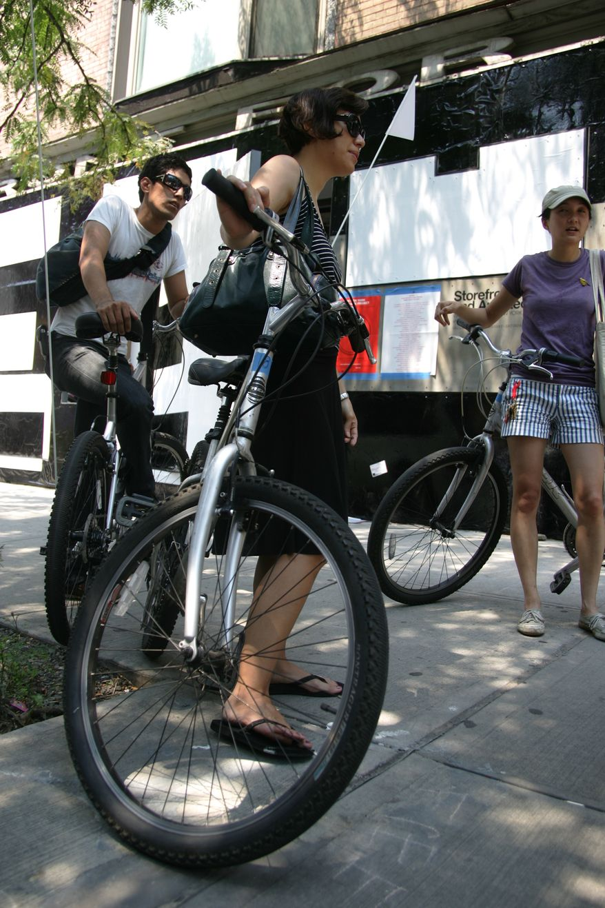 **FILE** James Vicente (left), Audrey Hawkins (center) and Julia Li borrow bicycles at the New York Bike-Share Project in the Storefront for Art and Architecture in New York on July 8, 2007. (Associated Press)