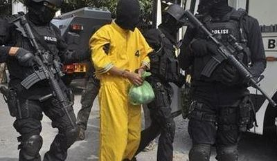 ** FILE ** An Indonesian police anti-terror unit Special Detachment 88 escorts a terror suspect after his arrest in Yogyakarta, Central Java, Indonesia, Sept. 28, 2012. (Associated Press)