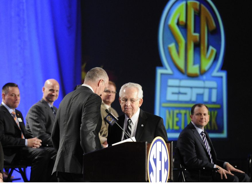 Southeastern Conference Commissioner Mike Slive, second from right, takes the podium after ESPN President John Skipper during a news conference announcing the launching of the SEC Network in partnership with ESPN, Thursday, May 2, 2013, in Atlanta. (AP Photo/John Amis)