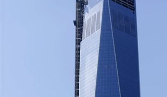 The final piece of the spire is hoisted to the roof of One World Trade Center, Thursday, May 2, 2013 in New York. The piece will be attached to the spire at a later date, capping off the tower at 1,776 feet. (AP Photo/Mark Lennihan)