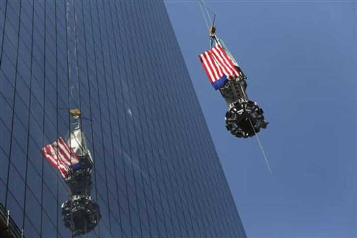 The final piece of the spire is hoisted to the roof of One World Trade Center, Thursday, May 2, 2013 in New York. The piece will be attached to the spire at a later date, capping o