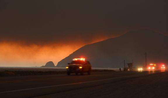 Fire department personnel drive along Pacific Coast Highway near Point Mugu as a thick layer of smoke sits overhead during a wildfire that burned several thousand acres, Thursday, May 2, 2013, in Ventura County, Calif.   (AP Photo/Mark J. Terrill)