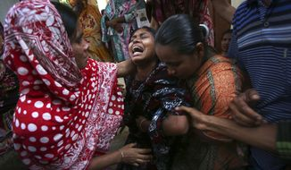 A woman is comforted by family members and others after she identified the body of her relative recovered from the rubble of the garment factory building which collapsed last week, in Savar, near Dhaka, Bangladesh, Friday, May 3, 2013. (AP Photo/Wong Maye-E)